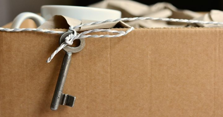 A packed cardboard box with a key hanging out of it